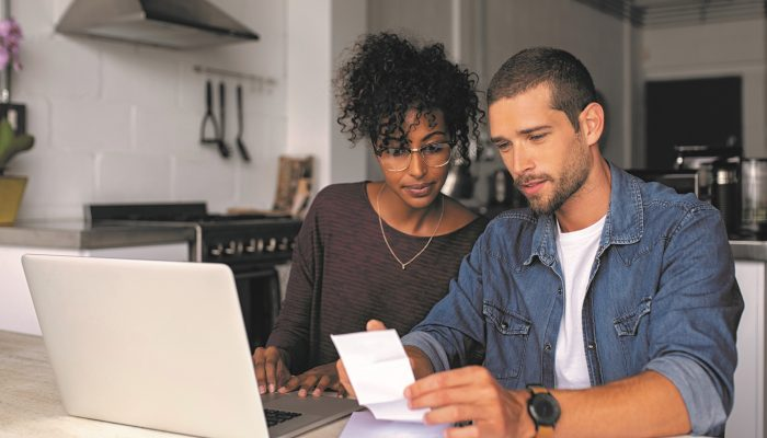 Man and Woman Look at Receipt In Front Of Computer